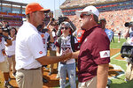 Clemson head coach Dabo Swinney, left, greets Texas A&M head coach Jimbo Fisher, while Jimbo's son Ethan, center, watches before the start of an NCAA college football game against Texas A&M Saturday, Sept. 7, 2019, in Clemson, S.C. (AP Photo/Richard Shiro)