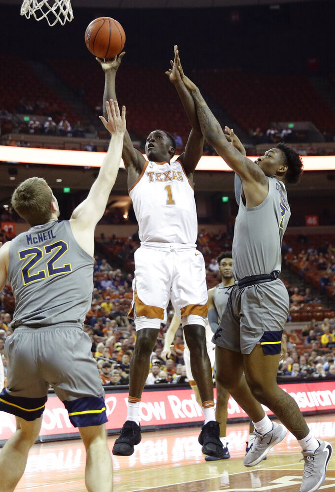 Texas guard Andrew Jones (1) shoots over West Virginia guard Sean McNeil (22) and forward Gabe Osabuohien (3) during the second half of an NCAA college basketball game, Monday, Feb. 24, 2020, in Austin, Texas. (AP Photo/Eric Gay)