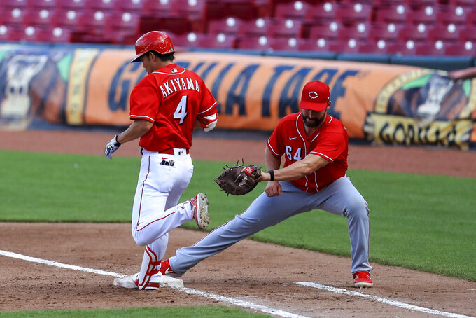 Cincinnati Reds' Shogo Akiyama (4) is out at first base as Matt Davidson (64) fields the ball during an intrasquad baseball game in Cincinnati, Tuesday, July 14, 2020. (AP Photo/Aaron Doster)