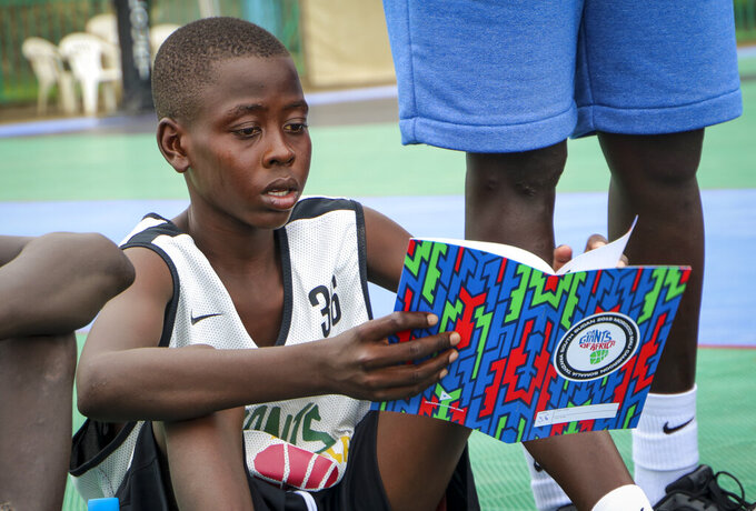 In this photo taken Tuesday, Aug. 20, 2019, a participant in the Giants of Africa basketball camp reads his career goals from a notebook while sitting on a basketball court in Juba, South Sudan. Masai Ujiri, president of the Toronto Raptors basketball team who won the NBA championship for the first time this year, is founder of the Giants of Africa non-profit organization which runs a three-day training camp in South Sudan to empower youth through basketball. (AP Photo/Sam Mednick)