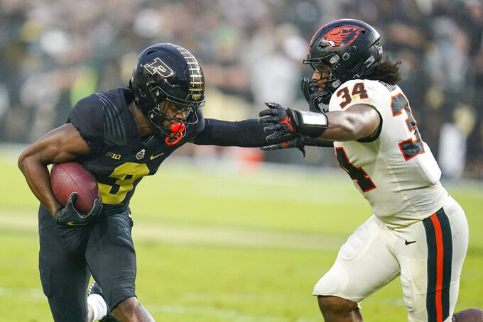 Purdue wide receiver David Bell (3) pushes off the tackle of Oregon State linebacker Avery Roberts (34) during the first half of an NCAA college football game in West Lafayette, Ind., Saturday, Sept. 4, 2021. (AP Photo/Michael Conroy)