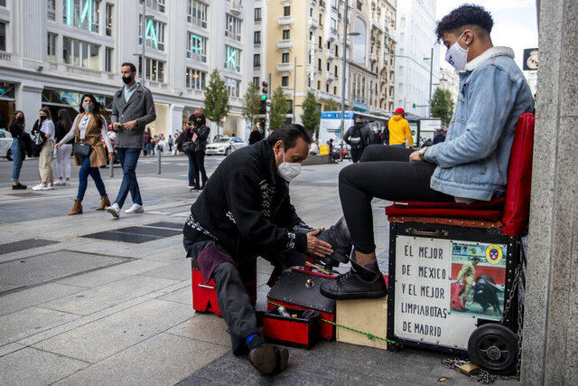 A shoe shiner wearing a face mask to prevent the spread of coronavirus cleans a shoes of a customer at Gran Via avenue in downtown Madrid, Spain, Saturday, Sept. 26, 2020. Spain's health minister has reiterated his plea for Madrid's regional authorities to apply more stringent restrictions on mobility in Europe's worst coronavirus hotspot. (AP Photo/Manu Fernandez)