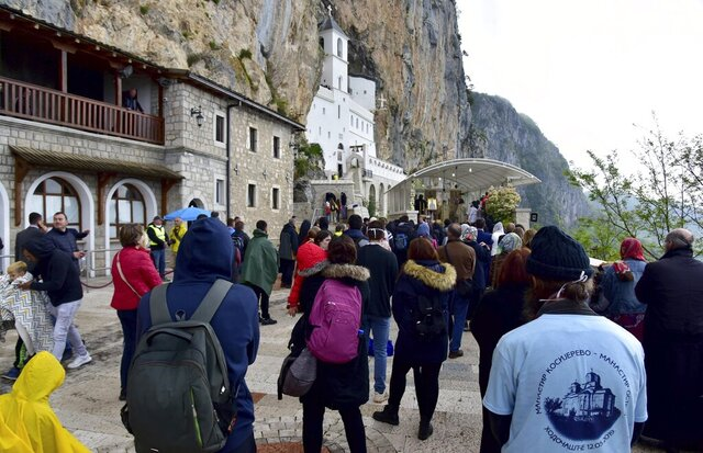 In this photo taken Tuesday, May 12, 2020, people wait in a queue in front of the Christian Orthodox monastery of Ostrog, 30 kilometers northwest of the Montenegrin capital Podgorica. Serbia has strongly protested the detention of eight Serbian Orthodox Church priests in Montenegro after thousands of people attended a religious procession despite a ban on gatherings because of the new coronavirus. Montenegrin prosecutors say that the priests are facing charges of violating health regulations during the virus outbreak by organizing the procession on Tuesday in the western town of Niksic. (AP Photo/Risto Bozovic)