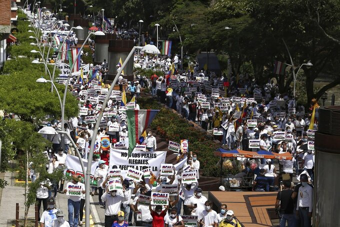People hold a silent march to support the unblocking of the city's main entrance and exit roads that have been blocked by anti-government protests in Cali, Colombia, Tuesday, May 25, 2021. Colombians have taken to the streets for weeks across the country after the government proposed tax increases on public services, fuel, wages, and pensions. (AP Photo/Andres Gonzalez)