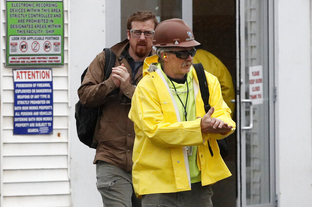 Workers rub their hands with hand sanitizer as they leave Bath Iron Works, Friday, April 3, 2020, in Bath, Maine. At least two workers at the defense contractor have been diagnosed with the coronavirus. (AP Photo/Robert F. Bukaty)