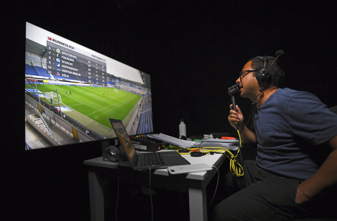 Soccer commentator Mark Scott commentates on the German Bundesliga soccer match between SC Paderborn 07 and TSG 1899 Hoffenheim remotely from a studio in Camden Town, London, Saturday May 23, 2020. The Bundesliga is the only soccer major league to have resumed since the start of the coronavirus lockdown and with increased global demand matches are also being provided to customers with a commentary in English. (AP Photo/Alberto Pezzali)