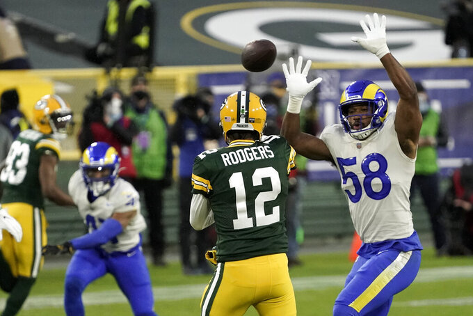 Los Angeles Rams' Justin Hollins (58) tries to block a pass by Green Bay Packers quarterback Aaron Rodgers during the first half of an NFL divisional playoff football game, Saturday, Jan. 16, 2021, in Green Bay, Wis. (AP Photo/Morry Gash)