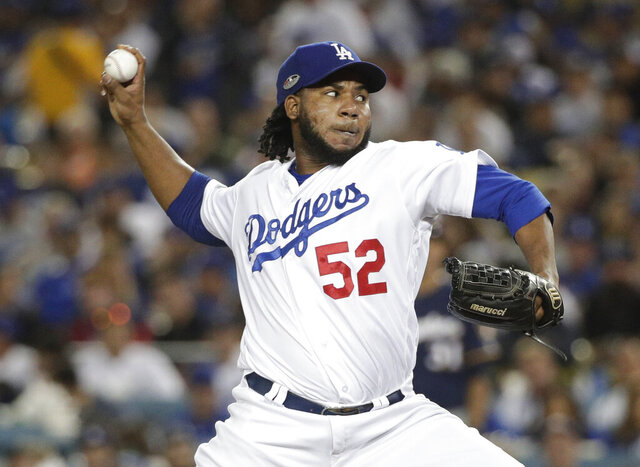 FILE - In this Tuesday, Oct. 16, 2018 file photo, Los Angeles Dodgers relief pitcher Pedro Baez throws during the sixth inning of Game 4 of the National League Championship Series baseball game against the Milwaukee Brewers in Los Angeles. Dodgers reliever Pedro Báez asked an arbitration panel for a raise to $4 million and Los Angeles argued during a hearing on Tuesday, Feb. 11, 2020 that he should be paid $3.5 million. (AP Photo/Jae Hong, File)
