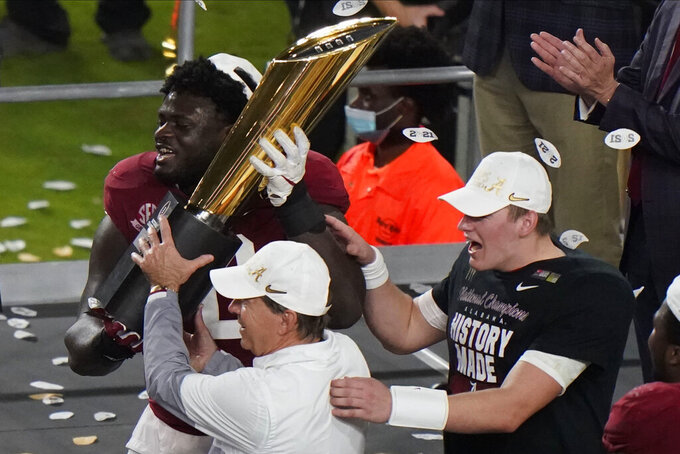 Alabama head coach Nick Saban and offensive lineman Alex Leatherwood hold the trophy after their win against Ohio State in an NCAA College Football Playoff national championship game, Tuesday, Jan. 12, 2021, in Miami Gardens, Fla. Alabama won 52-24. (AP Photo/Wilfredo Lee)