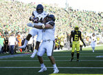 California's Christopher Brown Jr., left, celebrates his first quarter touchdown with teammate Jake Curhan as Oregon's Deommodore Lenoir looks on, right, during an NCAA college football game Saturday, Oct.. 5, 2019, in Eugene, Ore. (AP Photo/Chris Pietsch)