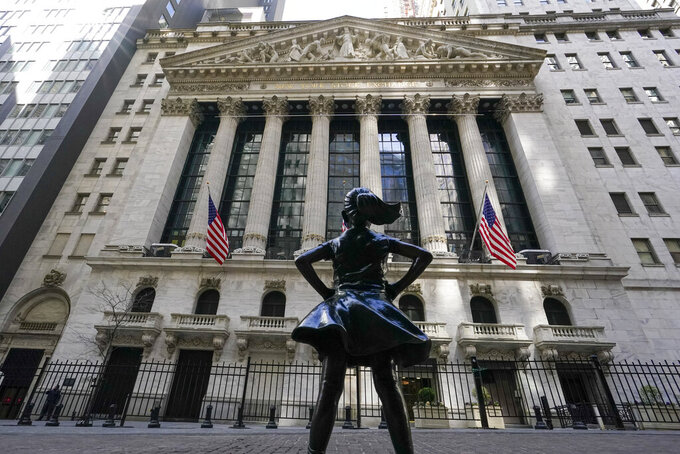 FILE - In this March 23, 2021 file photo, the Fearless Girl statue stands in front of the New York Stock Exchange in New York's Financial District. The global economic rebound from the pandemic has picked up speed but remains uneven across countries and faces multiple headwinds including the lack of vaccines in poorer nations. That could lead to new virus variants and more stop-and-go lockdowns, the Organization for Economic Cooperation and Development, OECD said in its latest forecast. (AP Photo/Mary Altaffer, File)