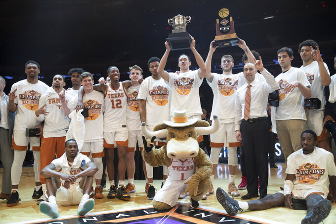 Texas players and coach Shaka Smart pose for photographers with their trophies after defeating Lipscomb during an NCAA college basketball game for the NIT championship Thursday, April 4, 2019, at Madison Square Garden in New York. Texas won 81-66. (AP Photo/Mary Altaffer)