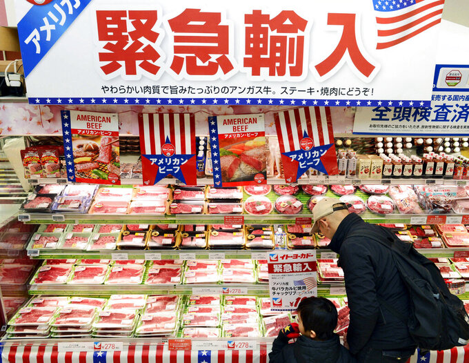 """FILE - In this Feb. 16, 2019, file photo, packs of frozen beef imported from the U.S. are sold at a supermarket in Tokyo. Imported American beef in Japan has proved so popular it's topped the annual limits called """"safeguards,"""" and the U.S. Meat Export Federation on Thursday, March 18, 2021 urged Tokyo to raise the threshold. Japan's import limit for American beef of 242,000 metric tons was reached in early March, and so tariffs will be raised from 25.8% to 38.5% for a month, starting Thursday through April 16, 2021. The banner at top reads: """"Emergency import from America."""" (Kyodo News via AP, File)"""
