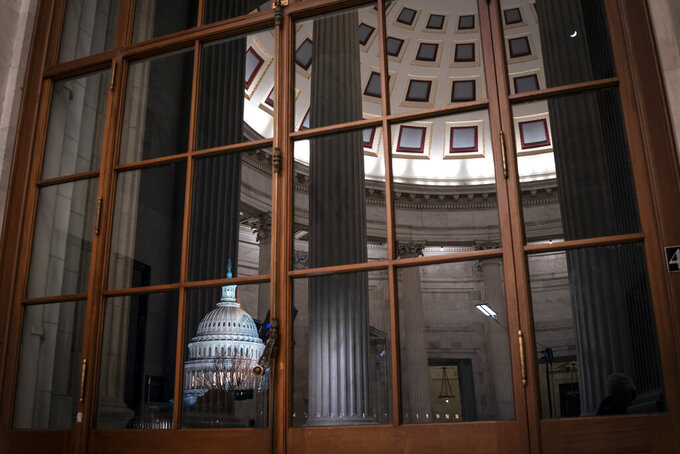 FILE - In this Jan. 29, 2020, file photo the Capitol is seen amid reflections of the Russell Senate Office Building in Washington. The Treasury Department said Wednesday, April 14, 2021, it has created a new office to supervise the disbursement of the billions of dollars in relief money passed by Congress to combat the coronavirus-related recession. Officials said the goal is to streamline the process and ensure that all eligible groups have access to the aid.  (AP Photo/J. Scott Applewhite, File)