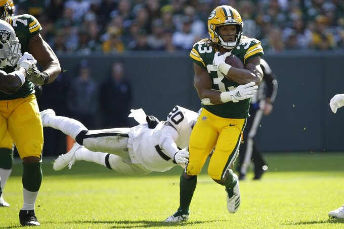 Green Bay Packers' Aaron Jones runs past Oakland Raiders' Daryl Worley during the first half of an NFL football game Sunday, Oct. 20, 2019, in Green Bay, Wis. (AP Photo/Mike Roemer)