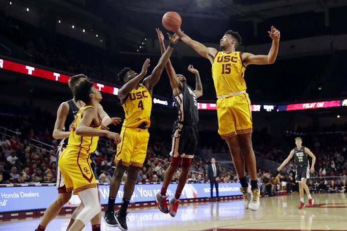 Southern California's Isaiah Mobley (15) grabs a rebound next to Washington State's Marvin Cannon during the second half of an NCAA college basketball game Saturday, Feb. 15, 2020, in Los Angeles. (AP Photo/Marcio Jose Sanchez)