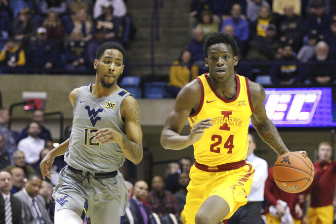 Iowa State guard Terrence Lewis (24) drives up court as he is defended by West Virginia guard Taz Sherman (12) during the first half of an NCAA college basketball game Wednesday, Feb. 5, 2020, in Morgantown, W.Va. (AP Photo/Kathleen Batten)
