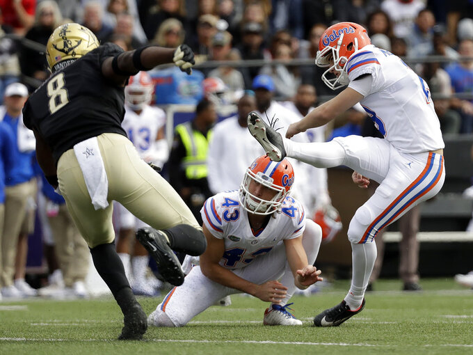 FILE - In this Oct. 13, 2018, file photo, Florida place kicker Evan McPherson, right, kicks a 43-yard field goal as Vanderbilt cornerback Joejuan Williams (8) rushes in the second half of an NCAA college football game, in Nashville, Tenn. Holding is Tommy Townsend (43). McPherson had made 12 of 13 field goals and all 27 extra points. (AP Photo/Mark Humphrey, File)