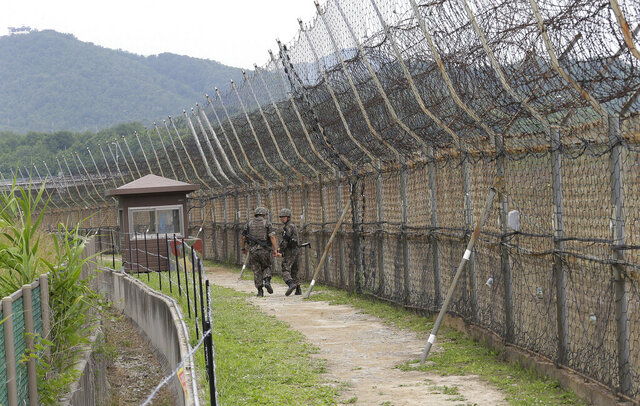 FILE - In this June 14, 2019, file photo, South Korean army soldiers patrol while hikers visit the DMZ Peace Trail in the demilitarized zone in Goseong, South Korea. South Korean troops were engaged in an operation near the heavily fortified border with North Korea on Wednesday, Nov. 4, 2020, after detecting