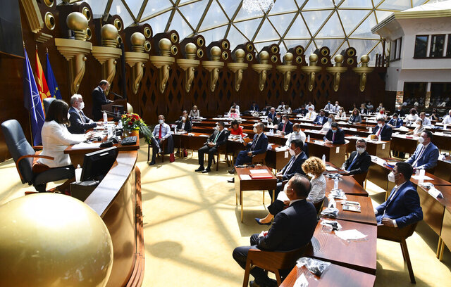 In this photo provided by  thePress Service of the Parliament of North Macedonia, lawmakers and candidates for ministers wearing face masks and social distancing to protect themselves from the coronavirus, attend the session of the Parliament dedicated for election of the new government, in a dome hall at the parliament building in Skopje, North Macedonia, Sunday, Aug. 30, 2020. North Macedonia's parliament continued its debate on a vote of confidence for a new left-wing coalition government after the Social Democrats and their ethnic Albanian partners secured a majority in parliament in July's general election. (Press Service of the Parliament of North Macedonia via AP)