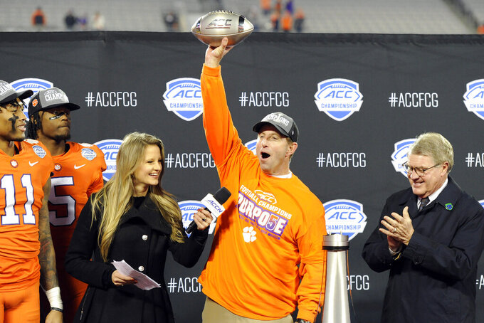 FILE - Clemson head coach Dabo Swinney, center, celebrates following the Atlantic Coast Conference championship NCAA college football game against Virginia in Charlotte, N.C., Saturday, Dec. 7, 2019. Even under normal circumstances, predicting what will happen in a college football season is an exercise in futility. Except for picking Clemson to win the Atlantic Coast Conference. (AP Photo/Mike McCarn, File)