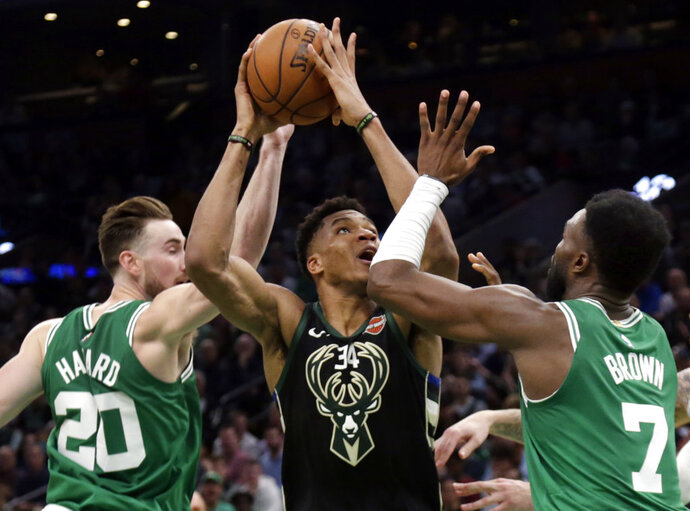 Milwaukee Bucks forward Giannis Antetokounmpo (34) goes to the hoop against Boston Celtics forward Gordon Hayward (20) and guard Jaylen Brown (7) in the second quarter of an NBA basketball game, Friday, Dec. 21, 2018, in Boston. (AP Photo/Elise Amendola)