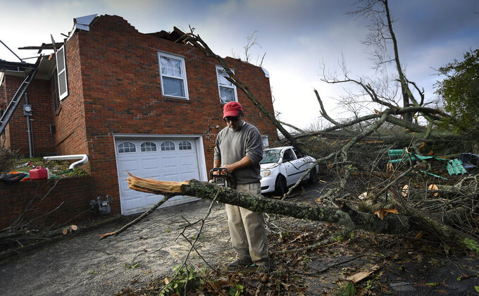 In this Tuesday, March 3, 2020 photo, Carlos Barquero cuts trees that damaged his home on Hunters Hill Rd. after a tornado ripped through the Donelson neighborhood in Nashville, Tenn. (George Walker IV/The Tennessean via AP)