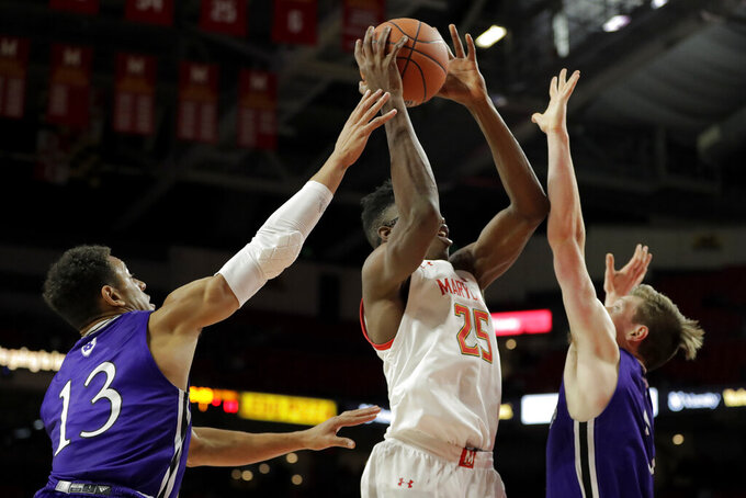 Maryland forward Jalen Smith (25) goes up for a shot against Holy Cross forward Marlon Hargis (13) and forward Connor Niego (5) during the first half of an NCAA college basketball game, Tuesday, Nov. 5, 2019, in College Park, Md. (AP Photo/Julio Cortez)