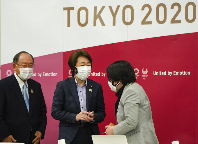 Seiko Hashimoto, center, President of the Tokyo 2020 Organizing Committee of the Olympic and Paralympic Games, talks with Kyoko Raita, right, Tokyo 2020 Executive Board member and speaker for a presentation on the Olympic Charter and Gender Equality in Tokyo, Japan, Monday, March 22, 2021. Fujio Mitarai, Honorary President of Tokyo 2020, is at left. Hashimoto said they will take all possible COVID-19 countermeasures as the torch relay opens this Thursday from northeastern Fukushima prefecture. (Kimimasa Mayama/Pool Photo via AP)