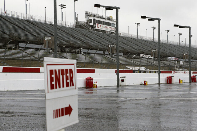 FILE - In this Sept. 2, 2016, file photo, empty grandstands are shown at Darlington Raceway after bad weather forced NSACAR to call off Friday, Sept. 2, 2016, in Darlington, S.C. Bad weather forced NASCAR to call off qualifying for the Sprint Cup and XFinity series auto races. NASCAR will have a much different feel when it resumes this weekend as the two-man broadcast team for Fox will not travel to Darlington Raceway and instead call the race from a studio in Charlotte.(AP Photo/Terry Renna, File)