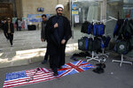 A cleric walks on the U.S. and British flags while leaving a gathering to commemorate the late Iranian Gen. Qassem Soleimani, who was killed in Iraq in a U.S. drone attack on Jan. 3, and victims of the Ukrainian plane that was mistakenly downed by the Revolutionary Guard last Wednesday, at the Tehran University campus in Tehran, Iran, Tuesday, Jan. 14, 2020. M (AP Photo/Vahid Salemi)