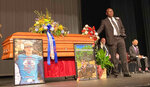 Attorney Ben Crump stands next to Hunter Brittain's casket at the Beebe High School Auditorium before his memorial service in Beebe, Ark. on Tuesday, July 6, 2021. Brittain was shot and killed by a Lonoke County Sheriff's deputy during a traffic stop June 23. (AP Photo/Andrew Demillo)