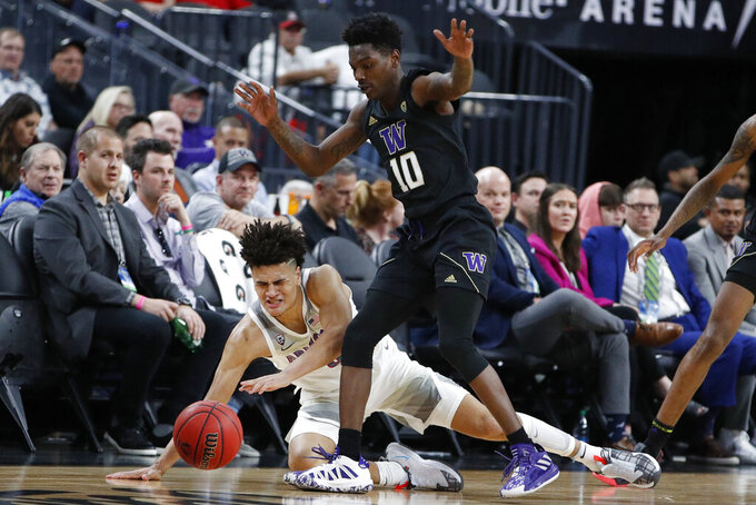 Arizona's Josh Green, left, and Washington's Elijah Hardy (10) battle for the ball during the first half of an NCAA college basketball game in the first round of the Pac-12 men's tournament Wednesday, March 11, 2020, in Las Vegas. (AP Photo/John Locher)