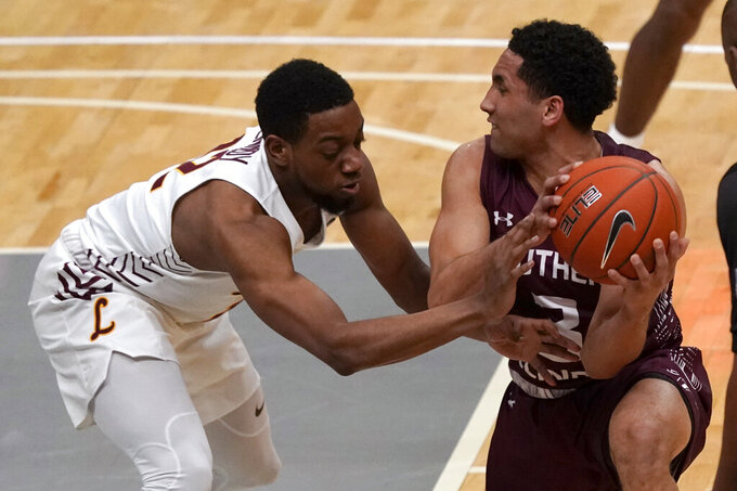 Southern Illinois' Dalton Banks, right, and Loyola of Chicago's Marquise Kennedy chase a loose ball during the first half of an NCAA college basketball game in the quarterfinal round of the Missouri Valley Conference men's tournament Friday, March 5, 2021, in St. Louis. (AP Photo/Jeff Roberson)