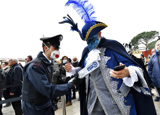 A policeman wearing a sanitary masks controls with a metal detector a reveler in Venice, Sunday, Feb. 23, 2020. Italian authorities have announced they are shutting down Venice's famed carnival events in a bid to stop the spread of the novel virus, as numbers of infected persons in the country have soared to at least 133, the largest amount of cases outside Asia. (AP Photo/Luigi Costantini)