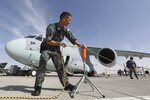 A Japanese crew fixes the rope around the Kawasaki C-2 transport aircraft during the opening day of Dubai Airshow in Dubai, United Arab Emirates, Sunday, Nov. 17, 2019. The biennial Dubai Airshow has opened as major Gulf airlines reign back big-ticket purchases after a staggering $140 billion in new orders were announced at the 2013 show before global oil prices collapsed. (AP Photo/Kamran Jebreili)