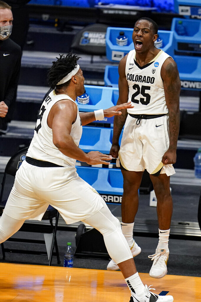 Colorado guard McKinley Wright IV (25) celebrates with forward Evan Battey (21) in the first half of a first-round game against Georgetown in the NCAA men's college basketball tournament at Hinkle Fieldhouse in Indianapolis, Saturday, March 20, 2021. (AP Photo/Michael Conroy)