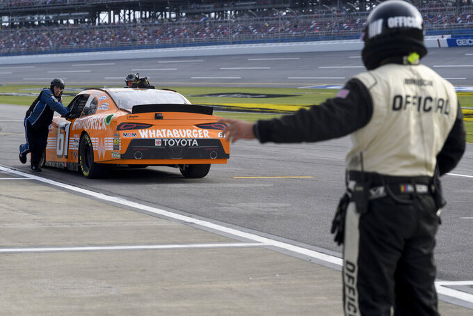 Crew members of a car driven by David Starr push it backward as an official directs them out of pit row during a NASCAR Xfinity Series auto race Saturday, Oct. 2, 2021, in Talladega, Ala. (AP Photo/John Amis)