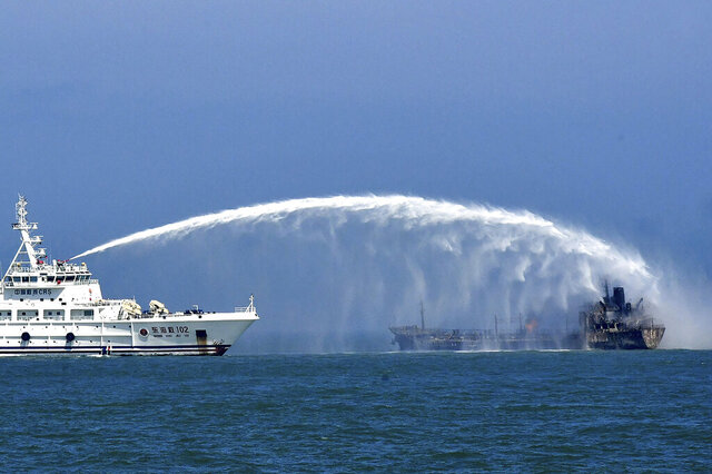 In this photo released by Donghai Rescue Bureau via Xinhua News Agency, a rescue vessel tries to put out fire emerging from an oil tanker after it collided with a cargo ship near the Yangtze River estuary off Shanghai, Thursday, Aug. 20, 2020. More than a dozen sailors were missing Friday, Aug. 21, 2020 after two ships collided in the Yellow Sea east of Shanghai, Chinese authorities reported. (Donghai Rescue Bureau/Xinhua via AP)