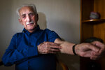 In this Friday, Jan. 10, 2020 photo Auschwitz survivor Leon Weintraub, 94, shows his arm where he has no identification number as he poses for a portrait in his apartment in Stockholm, Sweden. In 1940, his entire family was forced to live in the Lodz Ghetto from where they were deported to the Auschwitz concentration camp in 1944. Several weeks after arriving, he managed to escape by joining a group of inmates assigned to the Gross-Rosen concentration camp where he was forced to work as an electrician. To escape Auschwitz, he stripped off his prisoners' clothes to blend in to this group of naked prisoners who had just received their tattoos and were heading to pick up a new set of clothes. For this reason, he has no tattoo. He later learnt that all the other boys from his block in Auschwitz were killed in the gas chambers. (AP Photo/David Keyton)