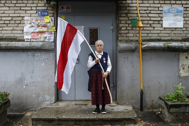 Nina Bahinskaya, 73, poses for a photo holding an old Belarusian national flag at an entrance of her apartment building in Minsk, Belarus, Thursday, Sept. 10, 2020. The 73-year-old former geologist has become one of the most recognizable faces of Belarus protests, fearlessly waving a huge opposition's red-and-white flag in front of riot police.
