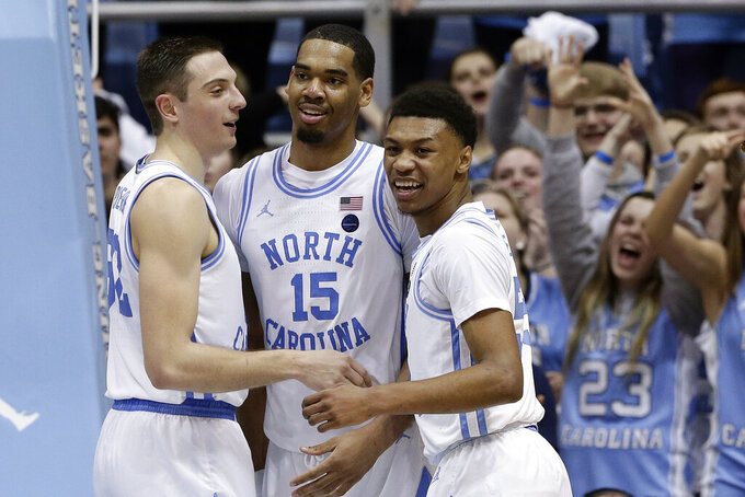 North Carolina guard Justin Pierce, left, forward Garrison Brooks (15) and guard Christian Keeling react following a play against North Carolina State during the second half of an NCAA college basketball game in Chapel Hill, N.C., Tuesday, Feb. 25, 2020. (AP Photo/Gerry Broome)