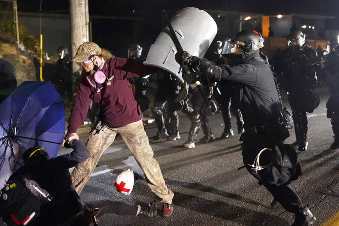A Portland police officer shoves a protester as police try to disperse the crowd in front of the Multnomah County Sheriff's Office early in the morning on Saturday, Aug. 8, 2020 in Portland, Ore. (AP Photo/Nathan Howard)