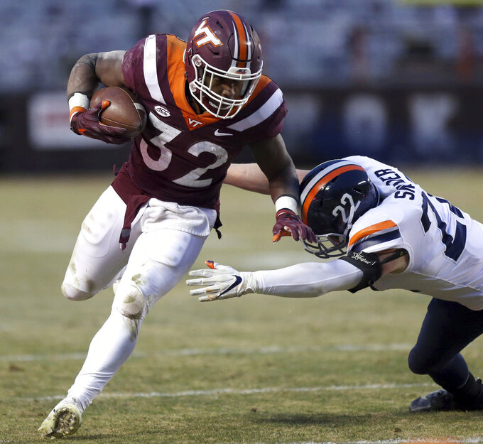 Virginia Tech running back Steven Peoples (32) is forced out of bounds by Virginia defender Chamarri Connor (22) during the first half of an NCAA college football game in Blacksburg, Va., Friday, Nov. 23, 2018. (Matt Gentry/The Roanoke Times via AP)