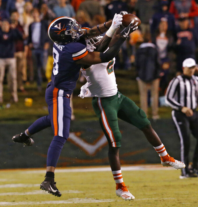 Miami defensive back Trajan Bandy (2) grabs an interception from Virginia wide receiver Hasise Dubois (8) during the first half of an NCAA college football game in Charlottesville, Va., Saturday, Oct. 13, 2018. (AP Photo/Steve Helber)