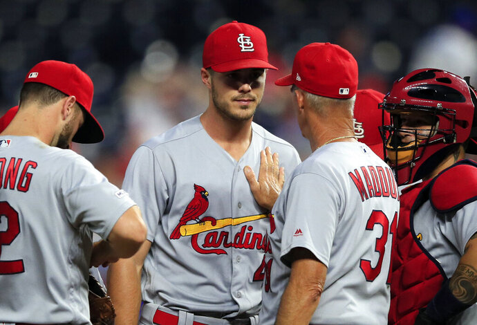 St. Louis Cardinals starting pitcher Dakota Hudson, facing camera, has a talk with pitching coach Mike Maddux (31) during the sixth inning of the team's baseball game against the Kansas City Royals at Kauffman Stadium in Kansas City, Mo., Wednesday, Aug. 14, 2019. (AP Photo/Orlin Wagner)