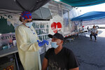 Nurse Tanya Markos administers a coronavirus test on patient Juan Ozoria at a mobile COVID-19 testing unit, Thursday, July 2, 2020, in Lawrence, Mass. (AP Photo/Elise Amendola)