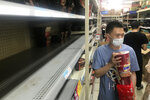 Shelves are empty as residents rush to stock up on necessities at a supermarket after authorities lockdown near residential blocks to prevent the spread of the COVID-19 in Wuhan city in central China's Hubei province Monday, Aug. 2, 2021. Chinese authorities announced Tuesday the mass testing of Wuhan as an unusually wide series of COVID-19 outbreaks reached the city where the disease was first detected in late 2019. (Chinatopix via AP)