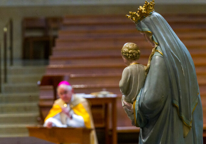 FILE - Archbishop Jose H. Gomez of Los Angeles and president of the U.S. Conference of Catholic Bishops (USCCB) kneels in prayer before the Blessed Virgin Mary, in Los Angeles Friday, May 1, 2020. (AP Photo/Damian Dovarganes, Pool, File)