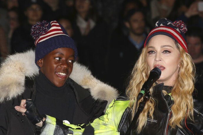 FILE- In this Nov 7, 2016 file photo, U.S. Singer Madonna, right, and her son David Banda perform in support of Democratic presidential candidate Hillary Clinton at Washington Square Park. The Queen of Pop is also a soccer mom and she's getting ever more involved in the beautiful game. Madonna has plans to open a soccer academy in Malawi, inspired by her adopted son David Banda who has ambitions to be a professional player and is at Portuguese club Benfica's youth academy. (Photo by Greg Allen/Invision/AP file)